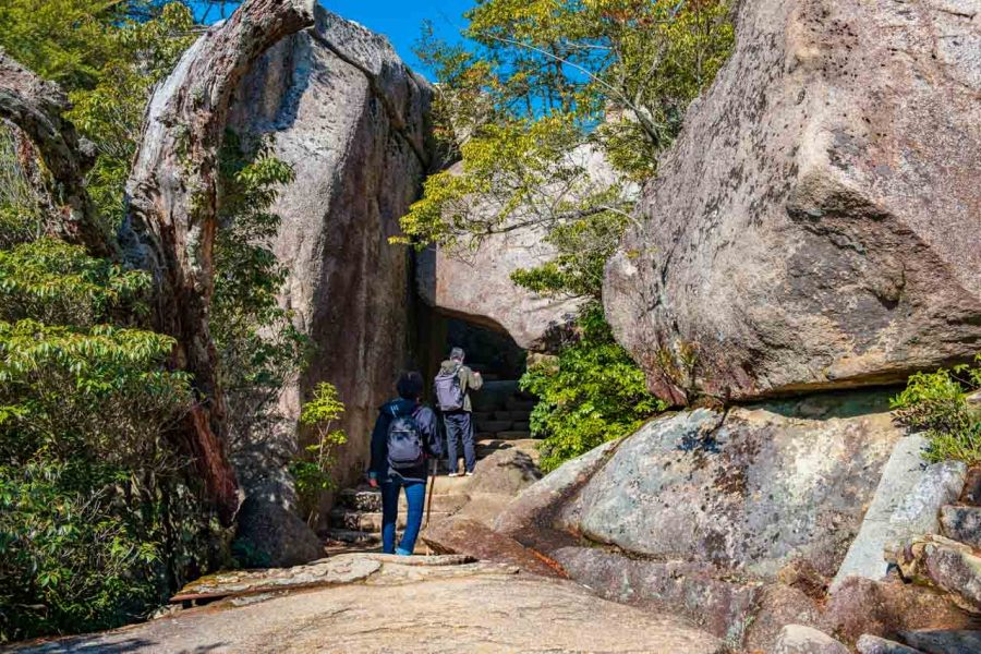 Hikers pass under large rock tunnel on Mt. Misen