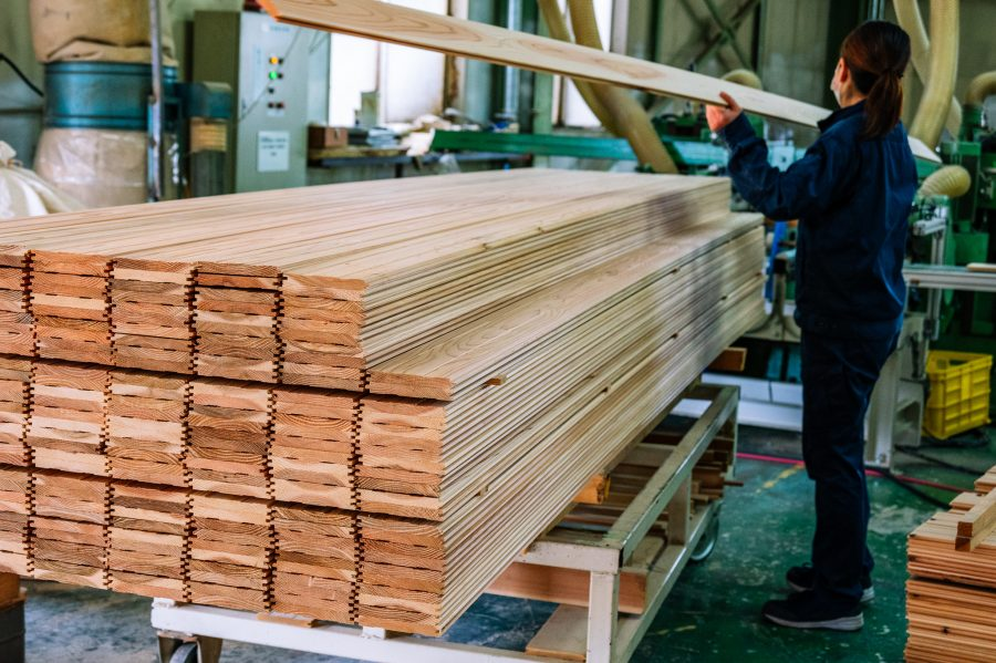woman stacks cedar flooring at a Japanese sustainable lumber factory