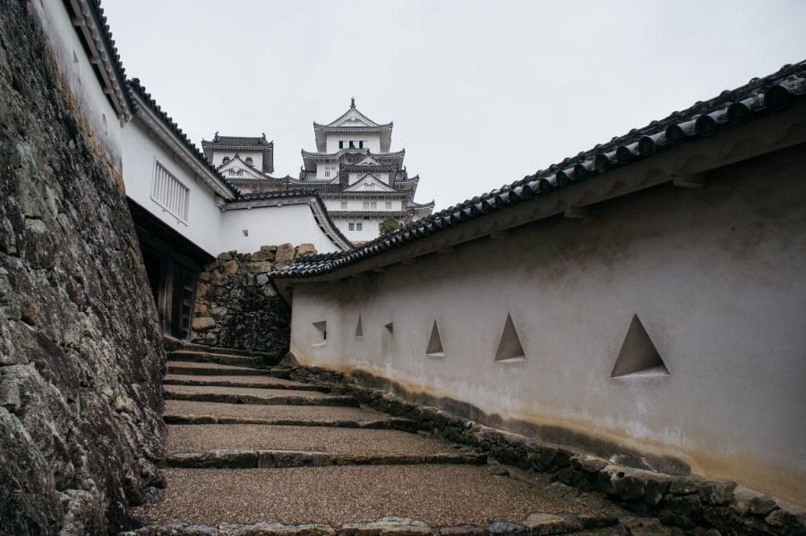 Allée menant au donjon d'un château japonais, aux murs percés de meurtrières géométriques