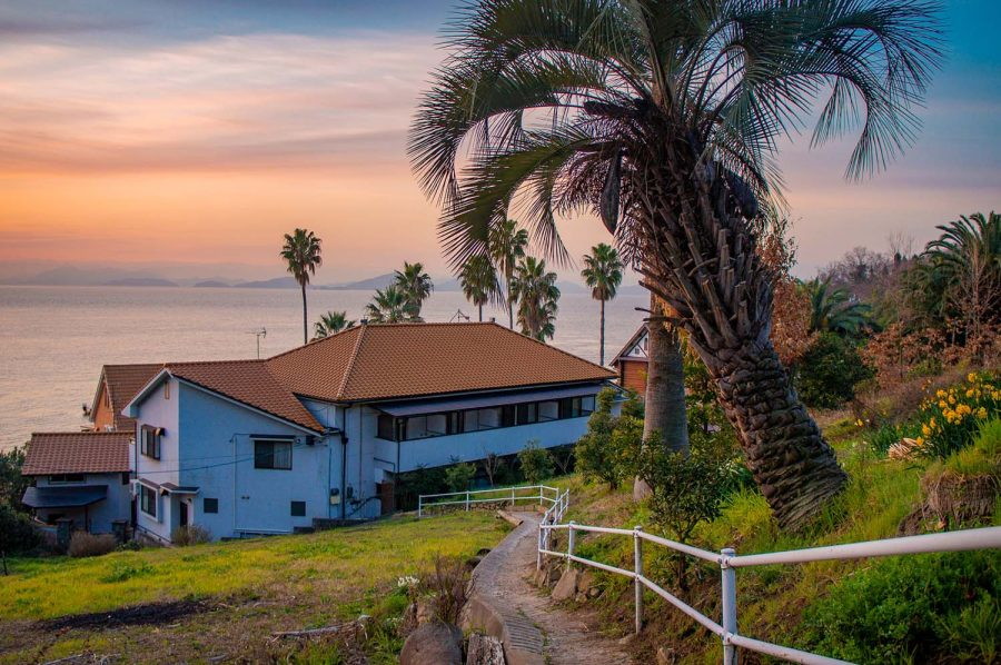 Japanese lodge surrounded by palm trees on an island in the Seto Inland Sea